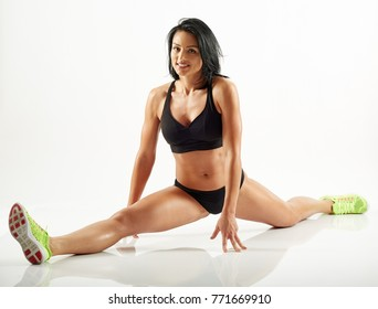 Young athletic hispanic woman doing a split on white background