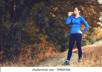 A young athletic jogger woman in a blue sports jacket with a hood and black  leggins drink water from the bottle after jogging on a colorful autumnall forest hill.