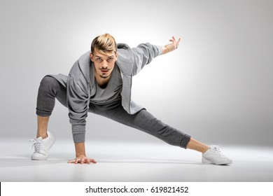Young athletic male dancer in sportswear posing while looking at camera