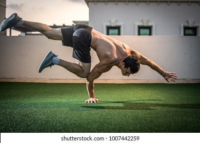 Young athletic man balancing while doing a one hand push up and holding his body in the air outdoors.