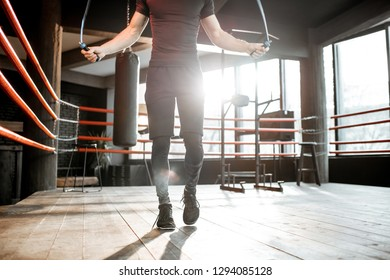 Young athletic man in black uniform training with a jumping rope, warming up on the boxing ring in the gym. Croppped image with no face