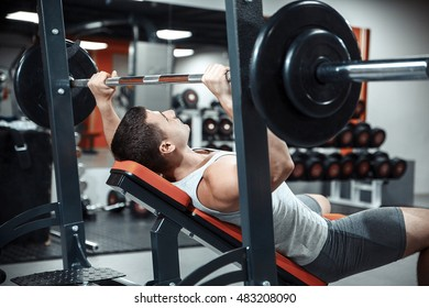Young athletic man bodybuilder doing bench press with heavy barbell in the gym. Focus on head.