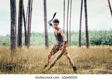 Young athletic man chopping wood in middle of forest. Dressed in undershirt and shorts with outdoor footwear and machete. In background out of focus grassy forest vegetation and trunks of other trees.