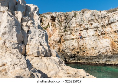 Young athletic man climbing sea cliffs without rope or harness in Croatia