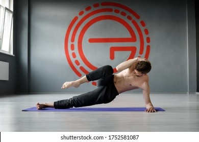 "Young, athletic man is doing exercise ""Side forearm plank with crunch to his knee""."