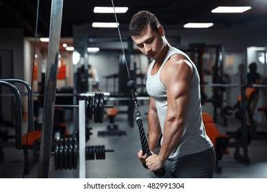 young athletic man doing exercise for triceps on block exerciser in gym.