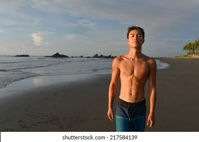 Young athletic man doing sport on the beach in the sand on the beach in the sun