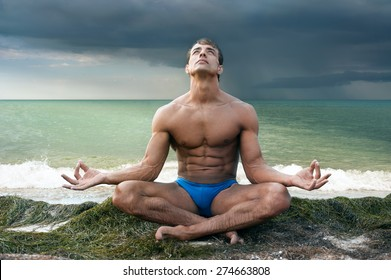 Young athletic man doing yoga on sea shore against seascape background