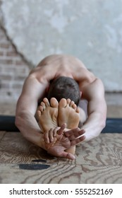 Young athletic man doing yoga and stretching on a mat on a wood floor with natural light and textured wall