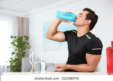 Young athletic man drinking protein shake at home, space for text