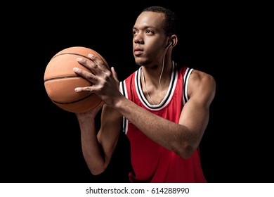 Young athletic man in earphones playing basketball  isolated on black