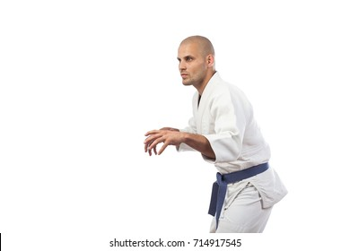 A young athletic man is a fighter in a white kimono for judo, jiu jitsu, sambo with a blue belt standing in a fighting rack on a white insulated background