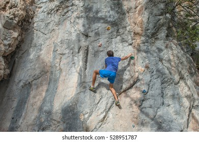 Young athletic man free climbing without equipment on dangerous rock slope