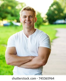 Young athletic man happy smiling. Coach man and strong guy portrait. In nature in the park in summer. Strength and motivation