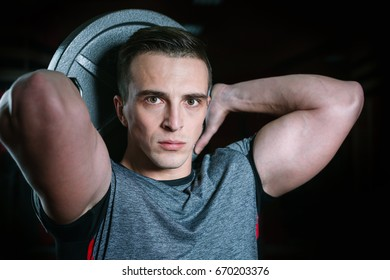 Young athletic man holding weights in studio. Serious facial expression.