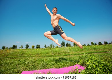 young athletic man jumping on grass