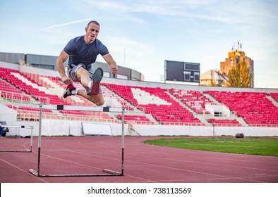 Young athletic man jumping over hurdles