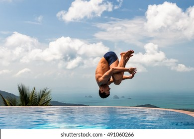 Young athletic man jumps into the pool at the top of the mountain