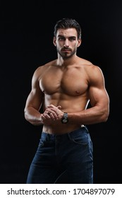 Young athletic man with a naked torso isolated on a black background.