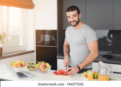 A young athletic man prepares a delicious salad of vegetables. He cuts the vegetables. A man is in a modern kitchen. On his arm is a fitness bracelet.