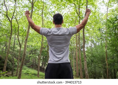 young athletic man raising arms in a forest. Sport and life achievements and success concept.