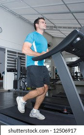 Young athletic man running on a treadmill at the gym