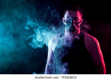 A young athletic man in a sports shirt breathes through a training black mask around a blue and red smoke cloud from a veip on a black isolated background