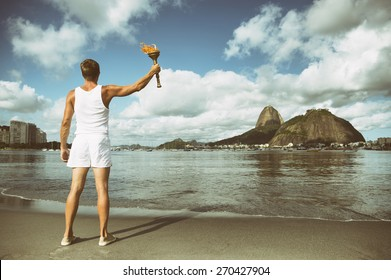 Young athletic man standing with torch against Rio de Janeiro Brazil skyline at Botafogo Bay with Sugarloaf Mountain
