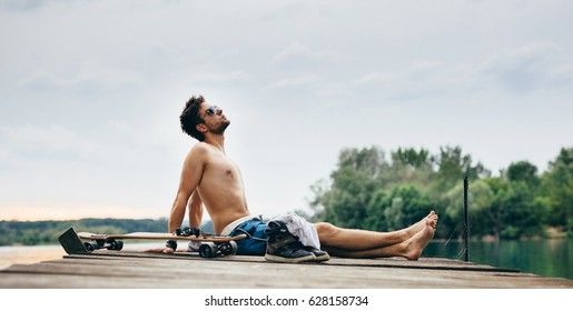 Young athletic man in swimsuit sitting on the end of the pier and sunbathing. Beside him a longboard, headphones and a part of his clothing including sneakers. Background, foreground out of focus.