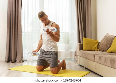 Young athletic man using bottles of water like an alternative of dumbbells for home workout
