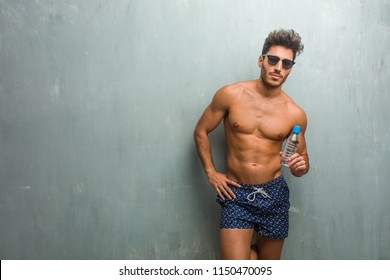 Young athletic man wearing a swimsuit against a grunge wall cheerful and with a big smile, confident, friendly and sincere, expressing positivity and success