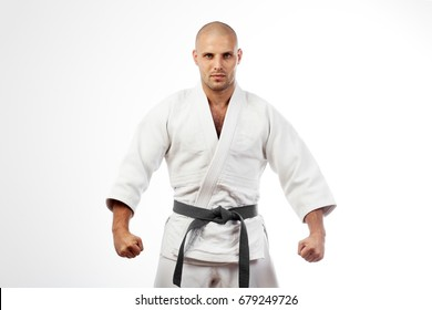 Young athletic man in white kimono for sambo, judo, jujitsu posing on white background, looking straight, position of fighting post, hands clasped in fist