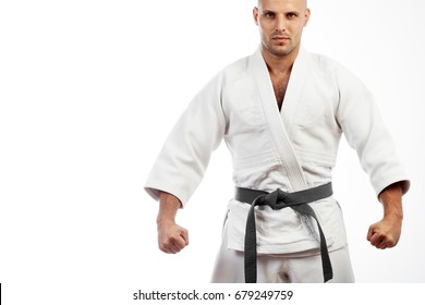 Young athletic man in white kimono for sambo, judo, jujitsu posing on white background, standing position, hands clasped in fist