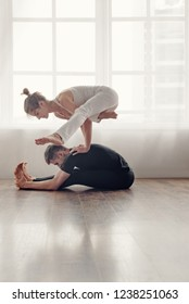 Young athletic man and woman doing yoga balance exercise