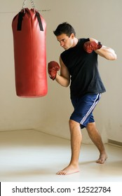 Young athletic man working out with a heavy punching bag. Isolated.