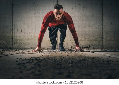Young, athletic man working out on a construction site in front of a concrete wall, getting ready for sprinting