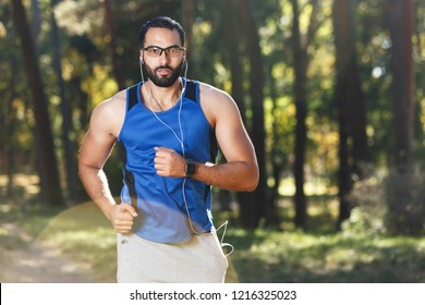 Young athletic multicultural bearded man wearing sportish glasses jogging and listening his favorite music, healthy lifestyle and people concept
