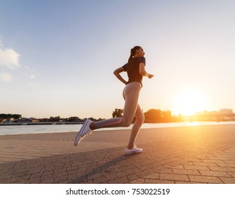 young athletic runner girl running around the river at sunset listening to music on headphones
