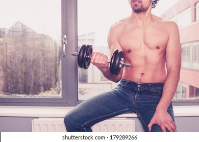 Young athletic shirtless man is working out by the window
