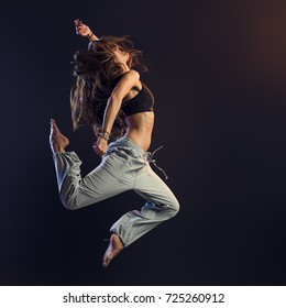 Young athletic slim dancer performing and jumping on dark background, fitness and vitality concept
