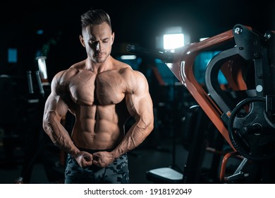 young athletic sportsman bodybuilder with muscle perfect body posing in gym