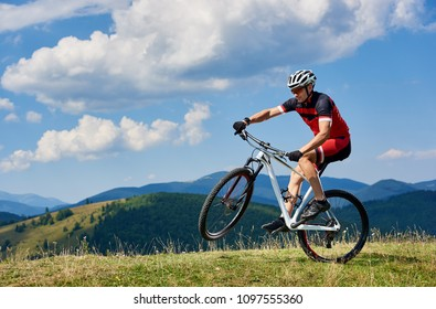 Young athletic sportsman tourist biker in professional sportswear turning on one wheel of bike on mountain hill on bright blue sky background. Active lifestyle and extreme sport concept.