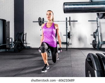 Young athletic sportswoman in sportswear exercising with dumbbells in gym