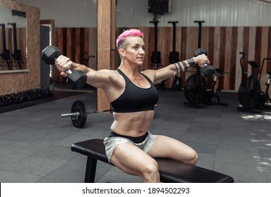 Young athletic strong woman trains the muscles of the shoulder with dumbbells in her hands while sitting on a bench in a cross gym. Bodybuilding and Fitness