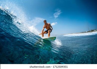 Junge sportliche Surfer reiten die Welle in Tropen mit Spritzen. Surfspot für Jailbreak auf den Malediven