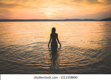 Young athletic tanned girl model walking in the sea. Feminine, attractive and sensual silhouette
