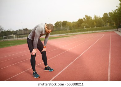 Young athletic tired sprinter having a break. Standing on a track catching his breath.