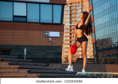 A young athletic woman in an attractive sports top and shorts is walking around the modern city in the summer.Concept of summer holidays at city and  sport livestyle