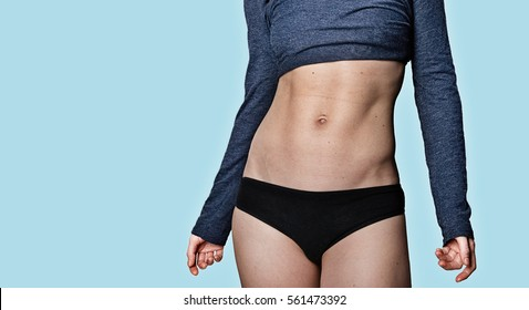 Young athletic woman belly on blue background. Front view. Close-up