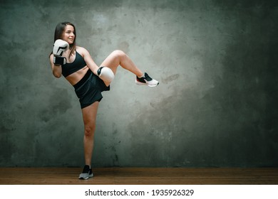 Young athletic woman boxer in shorts, short top and boxing gloves doing a kick above his head on dark gray background. Full length. Wall in background.